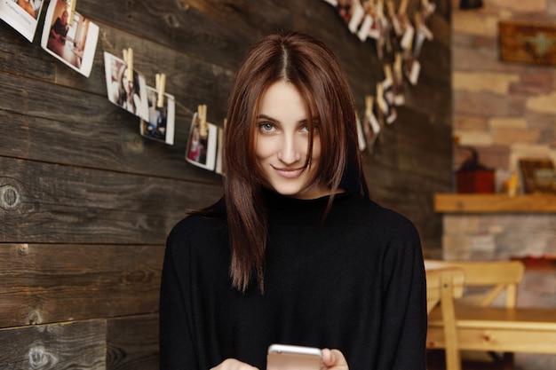 Jovem linda com sorriso encantador bonito relaxante no restaurante acolhedor, usando telefone celular, mensagens de texto