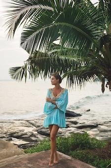 Jovem linda com um lindo vestido turquesa sob a palmeira durante as férias