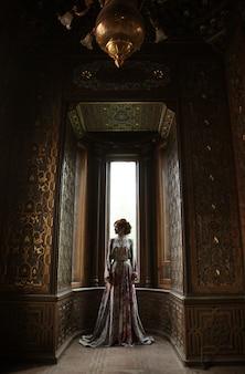 Jovem linda com um vestido rosa posando em um palácio de luxo