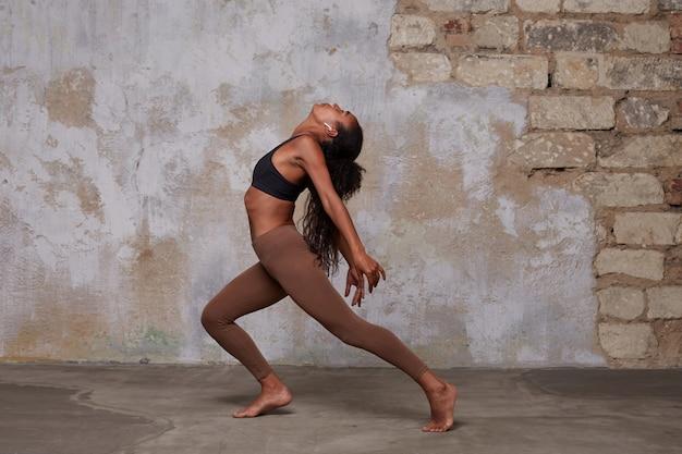 Jovem linda dançarina de pele escura usando seu cabelo comprido encaracolado em penteado de rabo de cavalo enquanto faz exercícios de dança, em pé sobre a parede de tijolos em uma roupa esportiva confortável