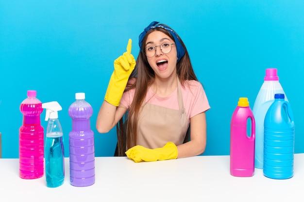 Jovem, linda dona da casa se sentindo um gênio feliz e animado depois de realizar uma ideia, levantando o dedo alegremente, eureka!