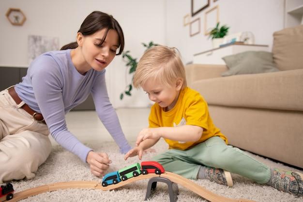 Jovem, linda e adorável garotinho loiro sentado no tapete fofo no chão, perto do sofá, brincando com o trem de brinquedo juntos em casa