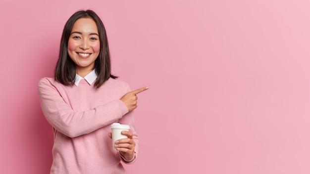 Jovem, linda e alegre mulher asiática com cabelo escuro sorrindo agradavelmente apontando para o lado no espaço em branco mostra o caminho para o café segurando bebida quente usa blusão casual