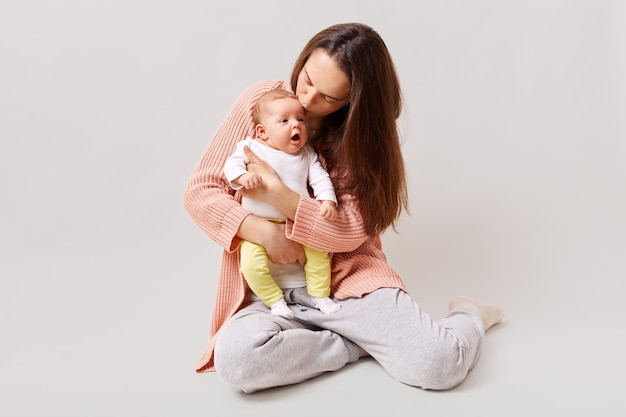 Jovem linda e atraente mãe segurando e beijando um bebê recém-nascido sentado no chão