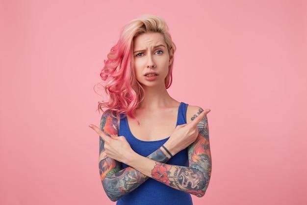 Jovem linda e desconectada senhora de cabelos rosa em camiseta azul, confusa e não consegue entender de que lado precisa, braços cruzados, aponta dedos em diferentes direções, levanta.