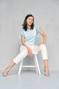 Jovem linda e feliz na blusa de cetim azul, calça jeans branca e estiletes prata sitts na cadeira branca no estúdio