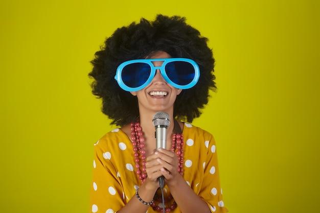 Jovem linda e sorridente com um penteado afro encaracolado e óculos engraçados cantando com o microfone sobre fundo amarelo