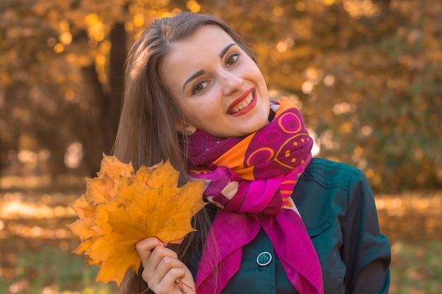 Jovem linda em scharfe sorrindo e segurando uma folha de bordo em sua mão, close-up