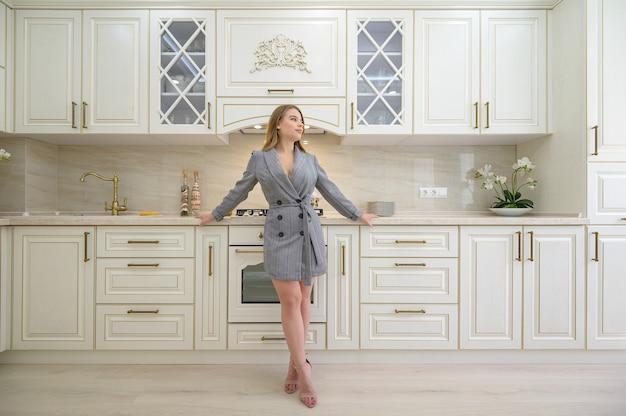 Jovem linda em uma cozinha bege clássica projetada em estilo provençal
