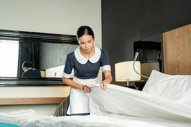 Jovem, linda empregada morena, colocando um cobertor branco limpo enquanto troca de cama em um dos quartos do hotel durante a preparação para novos hóspedes