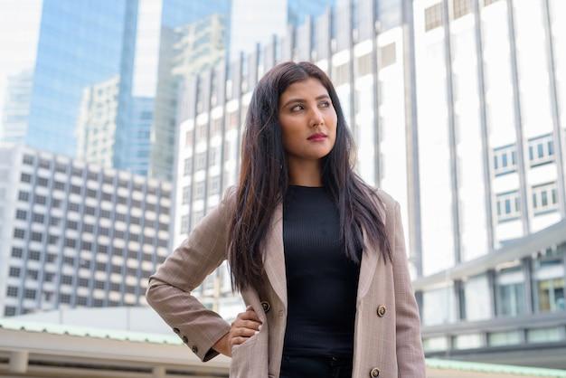 Jovem linda empresária indiana pensando na vista da cidade