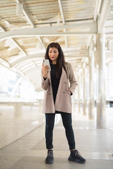 Jovem linda empresária indiana usando telefone na cidade