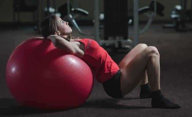 Jovem, linda, esportista fazendo exercícios em um fitball na academia