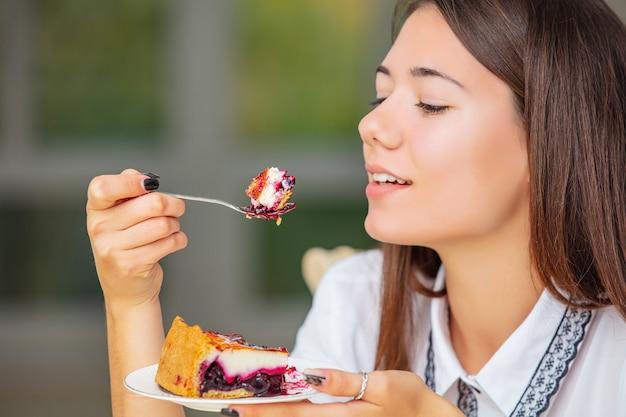 Jovem linda feliz desfrutando de um delicioso bolo de queijo doce fresco de perto