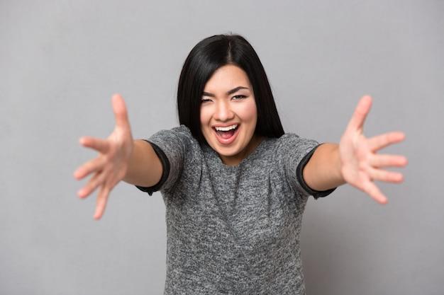 Jovem linda feliz sorrindo em um macacão cinza olhando para a mulher da frente com as mãos abertas, prontas para abraçar
