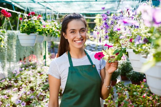 Jovem linda florista posando, sorrindo entre as flores.