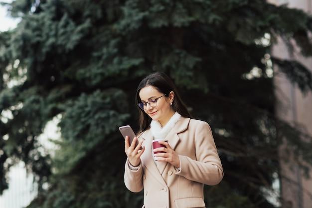 Jovem linda garota atraente com óculos aproveite o fim de semana na cidade com uma bebida quente na mão