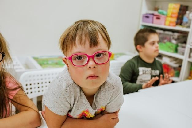 Jovem linda garota com síndrome de down, de camisa cinza e óculos cor de rosa, sentada na mesa branca com outras crianças e estudando.
