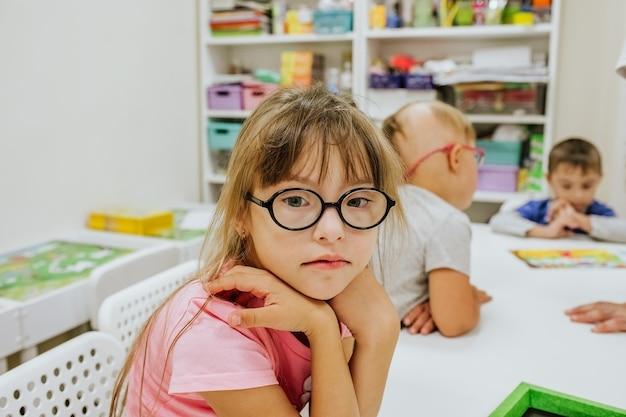Jovem linda garota com síndrome de down em uma camisa rosa e óculos escuros, sentada na mesa branca com outras crianças e estudando.