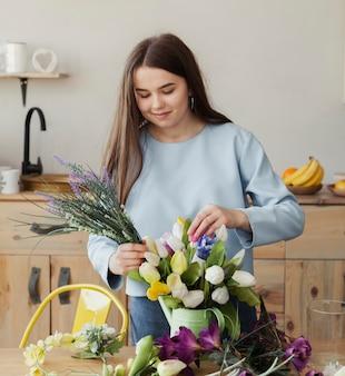 Jovem linda garota criando um buquê floral