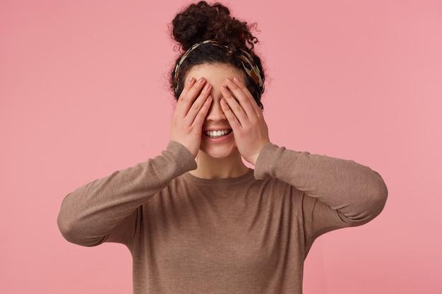 Jovem linda garota de cabelos cacheados cobriu o rosto com as mãos e sorri, esperando por uma surpresa. isolado sobre o fundo rosa.