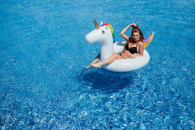 Jovem linda garota de cabelos castanho com uma boa figura bronzeado na piscina