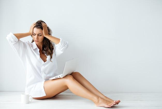 Jovem linda garota de pernas compridas em uma camisa masculina branca está sentada no chão com um laptop branco em uma sala com paredes brancas