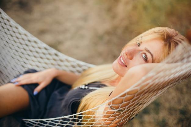 Jovem linda garota em um vestido curto preto verão encontra-se numa rede em uma floresta ou parque. camping, conceito.