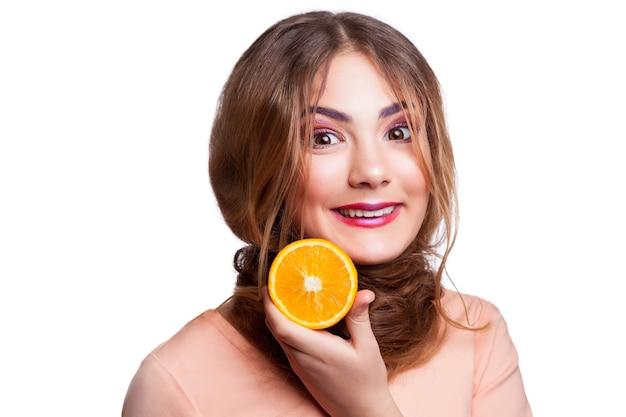 Jovem linda garota engraçada com uma fatia de laranja e maquiagem e penteado, olhando para a câmera. tiro do estúdio, isolado no fundo branco. .