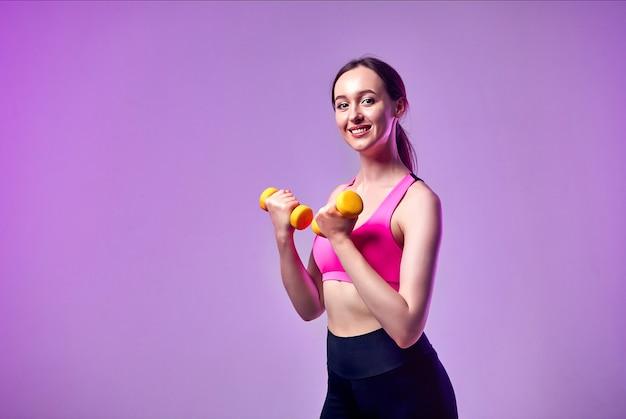 Jovem linda garota esportes em leggings e um top faz exercícios com halteres. estilo de vida saudável.