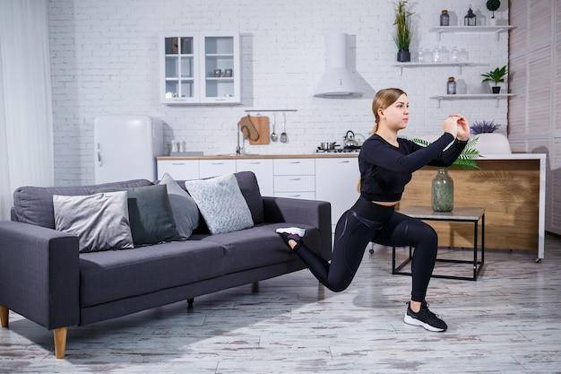 Jovem linda garota esportes em uma legging e um top faz exercícios em casa no sofá. estilo de vida saudável. a mulher pratica esportes em casa.