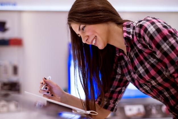Jovem linda garota feliz está experimentando o tablet de exibição em uma loja de tecnologia brilhante.