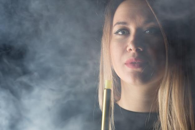 Jovem, linda garota fuma um cachimbo de água