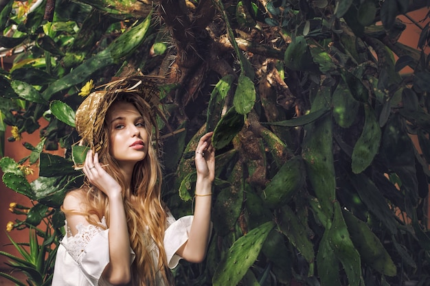 Jovem linda garota loira feliz no fundo de um enorme cacto com um chapéu