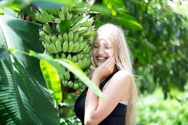 Jovem linda garota loira parada perto de uma bananeira