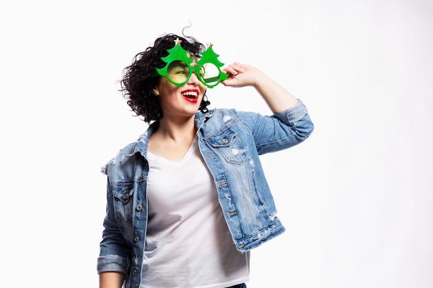 Jovem linda garota morena rindo em jeans e vidros decorativos sob a forma de uma árvore de natal. humor e diversão de ano novo.