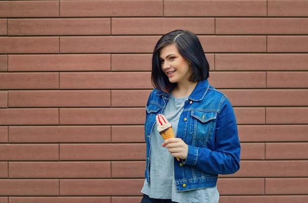 Jovem linda garota segurando uma casquinha de sorvete com geleia na mão. mulher em uma parede de tijolos na rua com uma jaqueta jeans