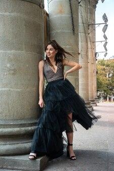 Jovem linda garota usando vestido em superfície urbana