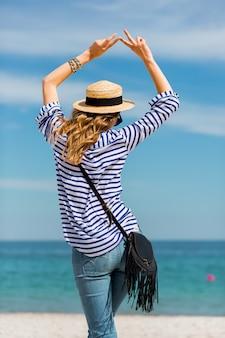 Jovem linda loira bronzeada jovem em pé na praia perto do mar de volta esperando e sonhando com