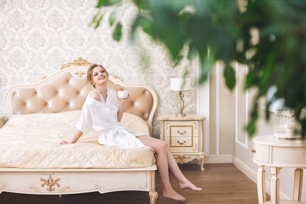 Jovem, linda, luxuosa, feliz, em lingerie branca, no quarto, no interior do designer, na cama