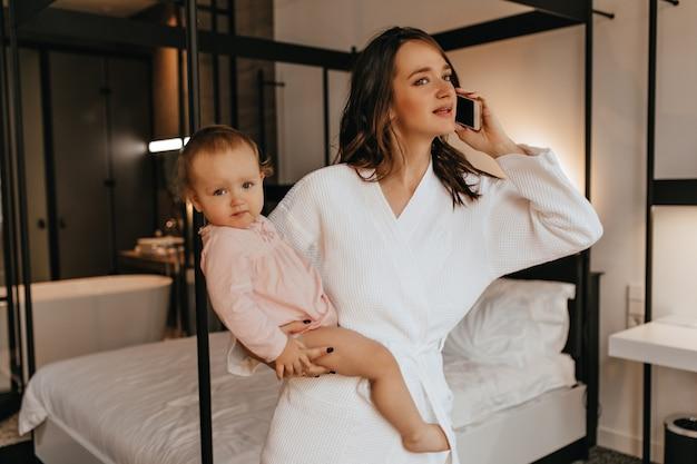 Jovem linda mãe com roupão de banho branco, segurando a filha nos braços e falando no telefone no quarto.