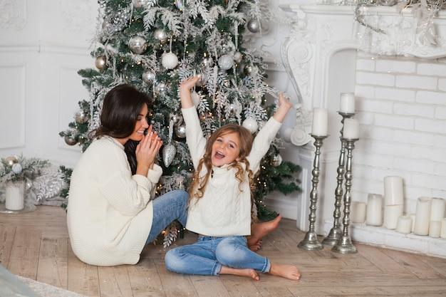 Jovem linda mãe e filha pequena em suéteres brancos aconchegantes e cobertor se divertem e se abraçam debaixo de uma árvore de natal decorada. interior clássico em casa festivo.