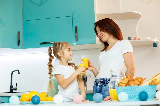 Jovem linda mãe e sua filha brincando na cozinha durante o café da manhã em casa.