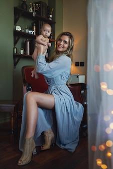 Jovem linda mãe usando um vestido cinza luxuoso, sentada na poltrona e segurando o bebê nas mãos