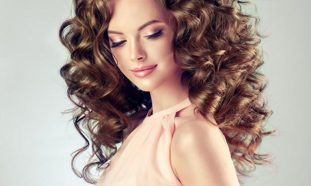 Jovem, linda modelo com penteado ondulado, denso e exuberante, sorriso atraente e terno nos lábios.