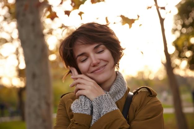 Jovem linda morena com penteado bob, segurando a palma da mão levantada na bochecha e sorrindo alegremente com os olhos fechados, em pé sobre o parque desfocado