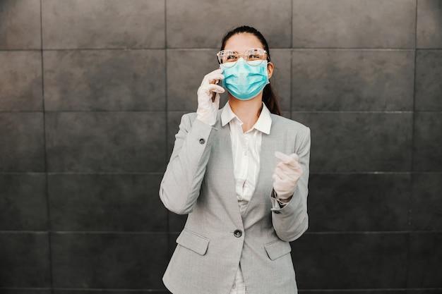 Jovem linda morena feliz vestida smart casual com máscara facial e luvas de borracha em pé ao ar livre e tendo conversa por telefone durante o surto de vírus cobiçoso.