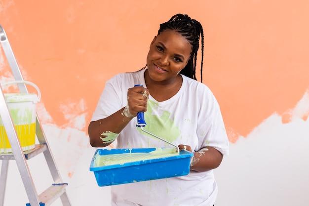 Jovem linda mulher afro-americana, pintura de parede em seu novo apartamento. renovação e