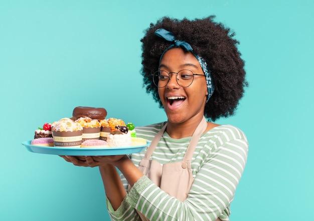 Jovem, linda mulher afro, padeiro com bolos