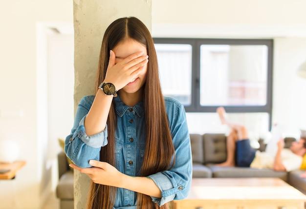 Jovem, linda mulher asiática, parecendo estressada, envergonhada ou chateada, com dor de cabeça, cobrindo o rosto com a mão
